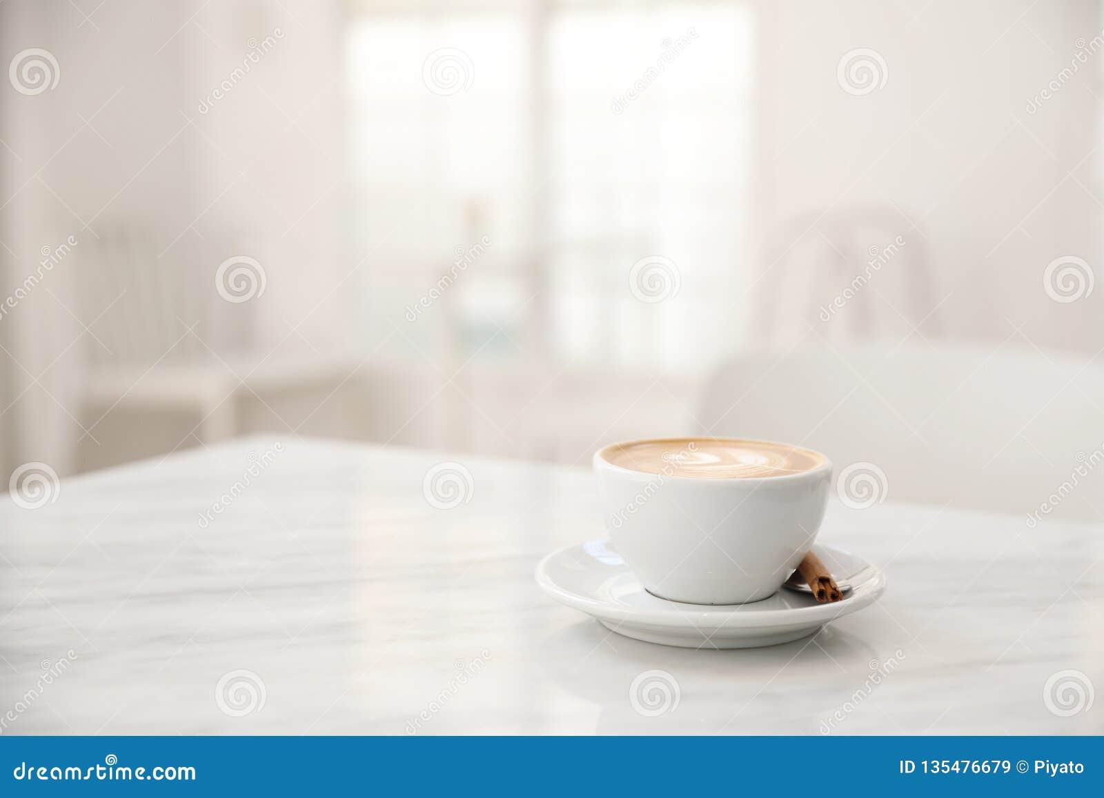 CappuccinoKaffeetasse auf weißer Marmortabelle