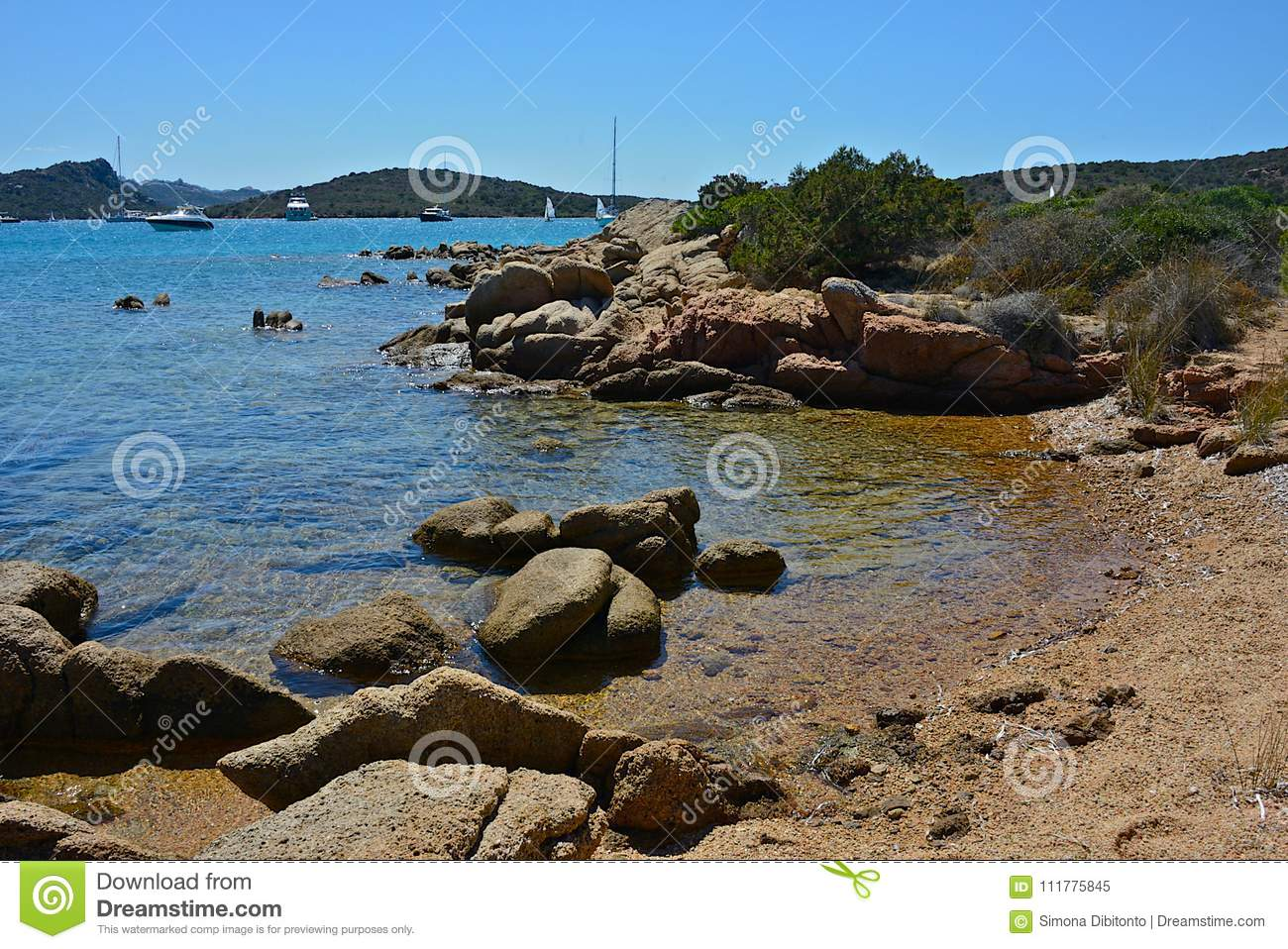 Seascape with sandy beach, blue sea and sky and some boats moored
