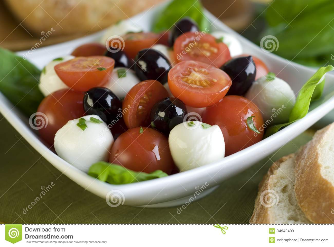 Fresh, healthy salad with tomato, mozzarella, basil and olives.