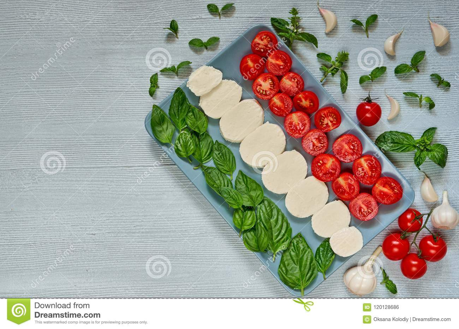 Caprese salad with organic ingredients: mozzarella cheese, cherry tomatoes, fresh basil leaves, garlic. Traditional italian food