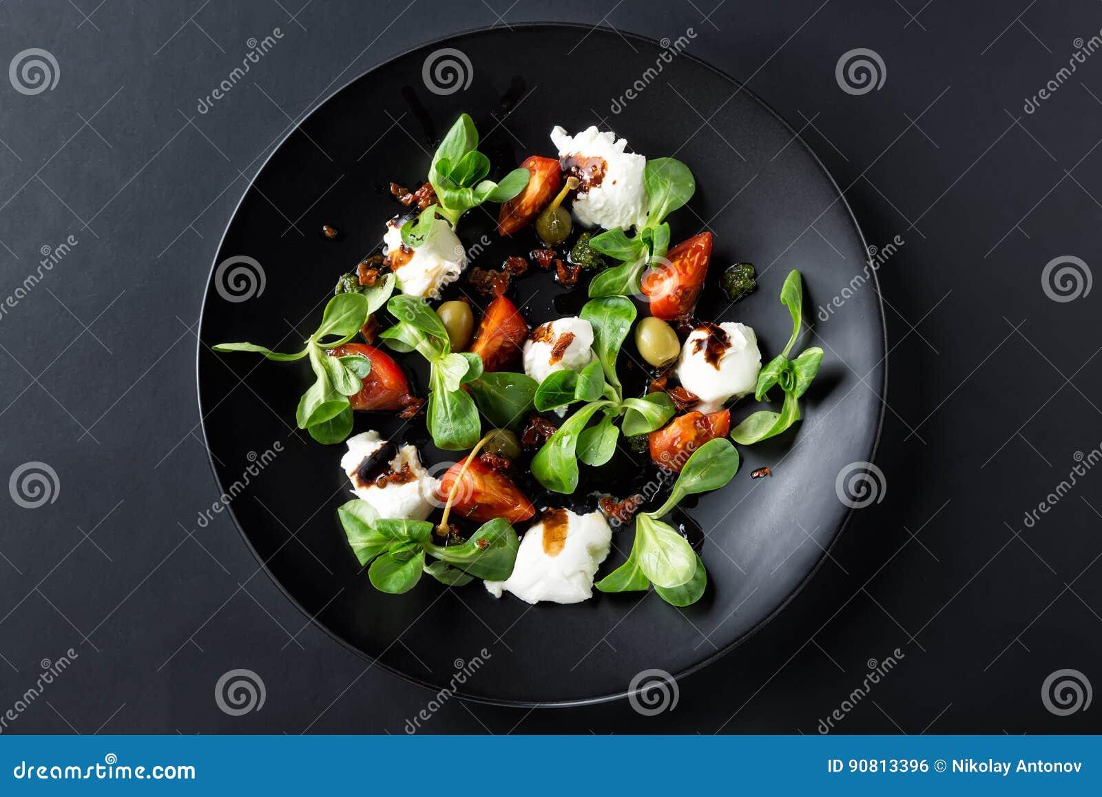 Caprese sallad med mozzarellaen, tomaten, basilika och balsamic vinäger som är ordnade på den svarta plattan och mörkerbakgrund T