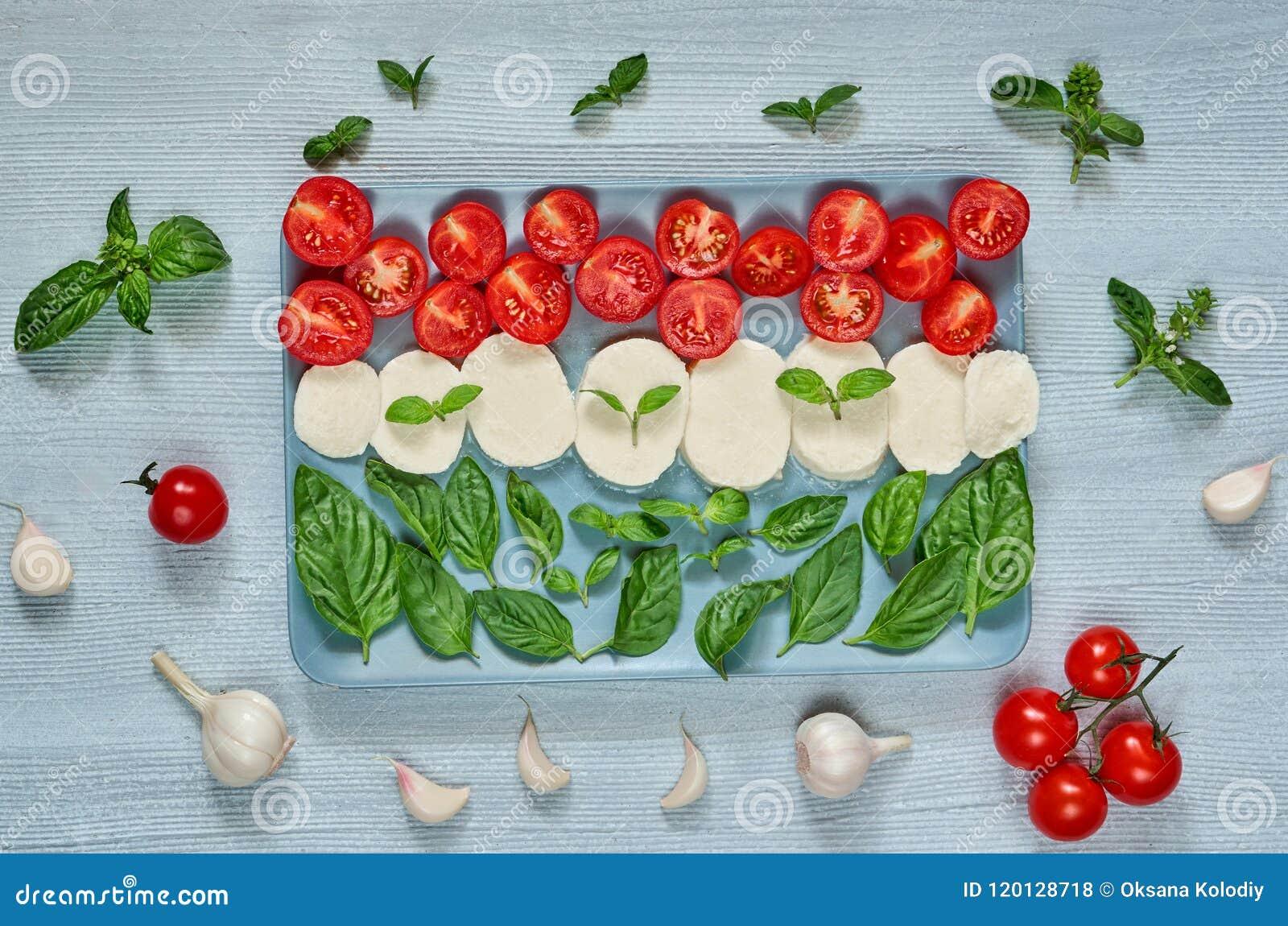 Caprese sallad med organiska ingredienser: mozzarellaost, körsbärsröda tomater, nya basilikasidor, vitlök traditionell matitalien