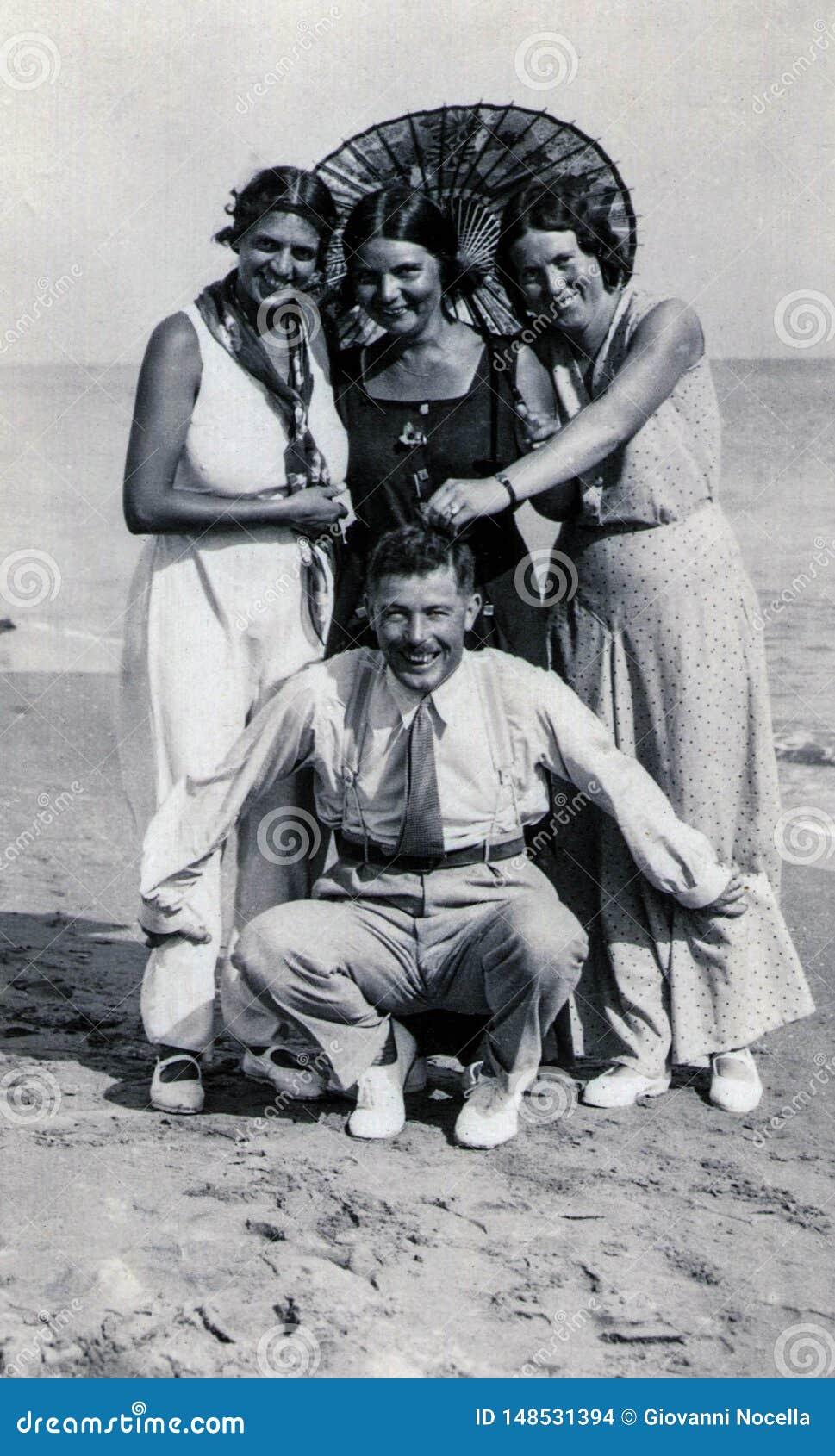 Capri, Włochy, 1933 - Trzy garbnikującej dziewczyny i ich frind żartują na plaży