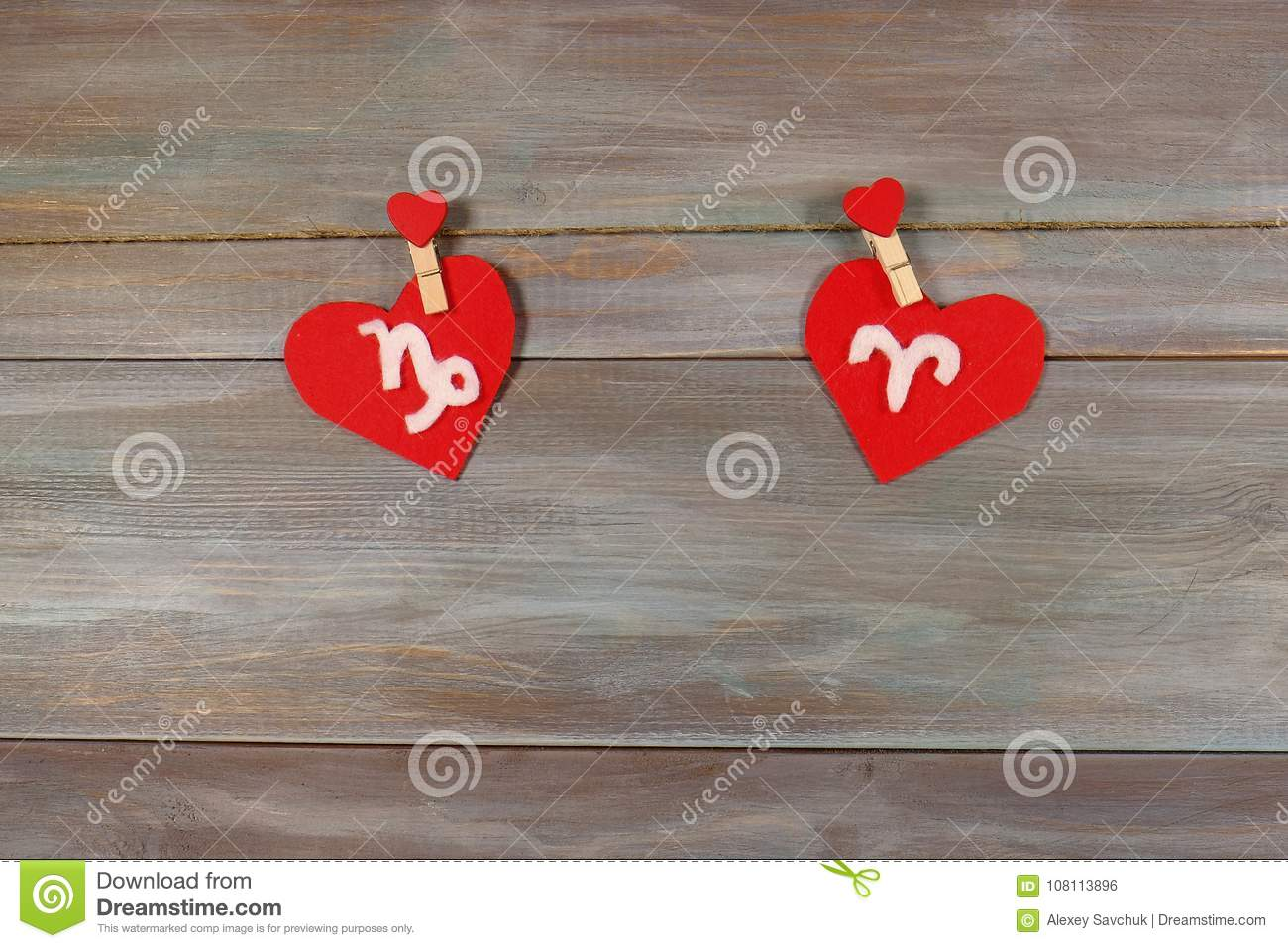 Capricorn and Aries. signs of the zodiac and heart. wooden backg