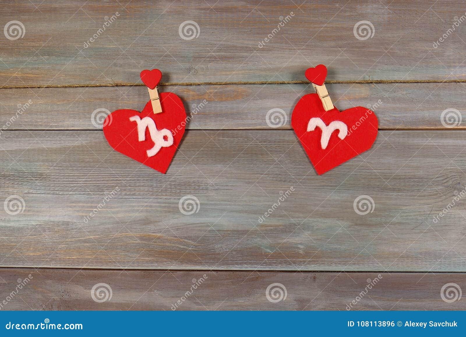 Capricorn i Aries znaki zodiak i serce drewniany backg