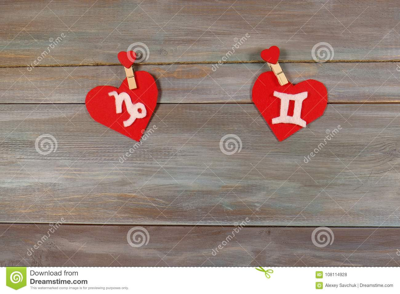 Capricorn and twins. signs of the zodiac and heart. wooden backg