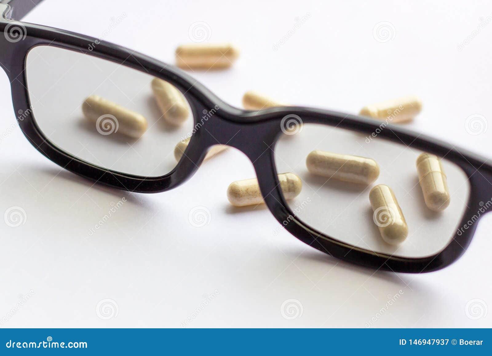 Capsule con i vetri su fondo leggero Farmacia e medicina per il concetto degli occhi