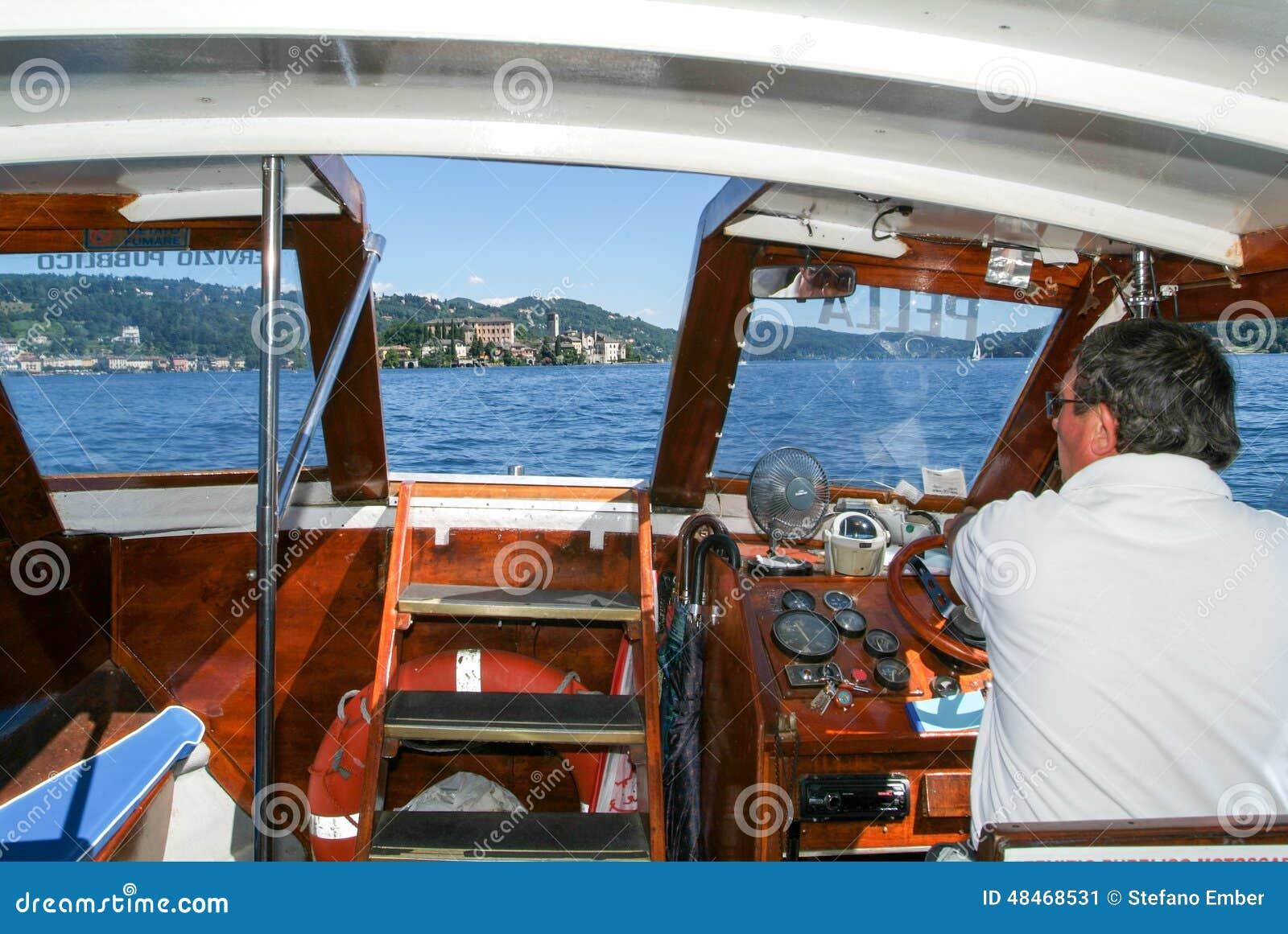 captain conduire un bateau devant l 39 le de san giulio photo ditorial image 48468531. Black Bedroom Furniture Sets. Home Design Ideas