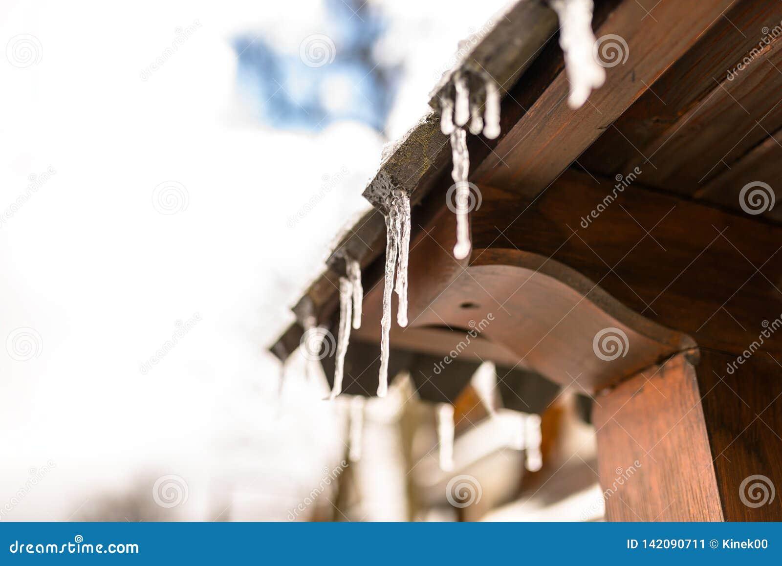 Carámbanos colgantes del tejado de un edificio de madera en un día escarchado del invierno, mucha nieve en el tejado