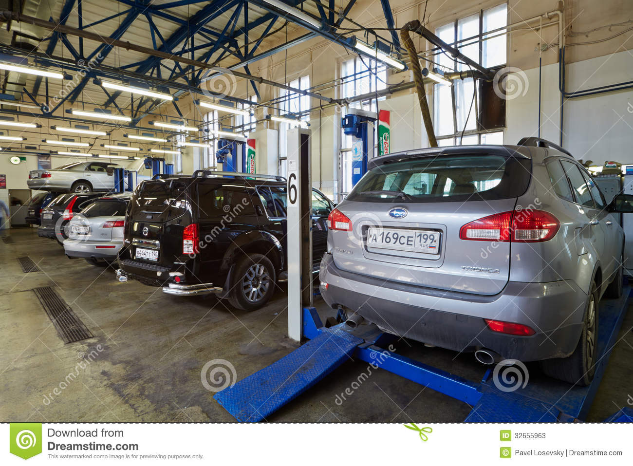 car on base plate of four post lift in workshop editorial stock photo