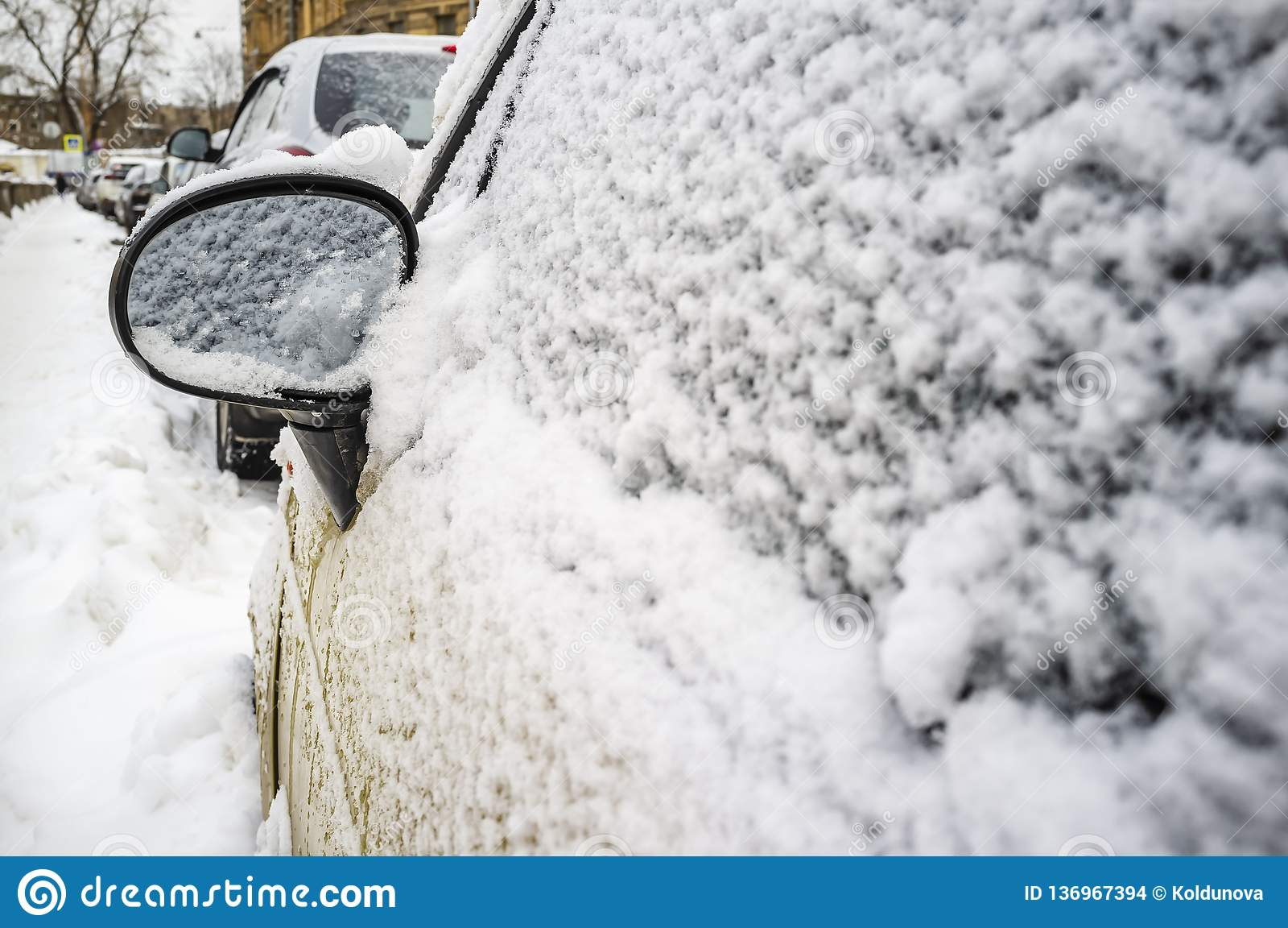 Car covered with snow and a rearview mirror close-up