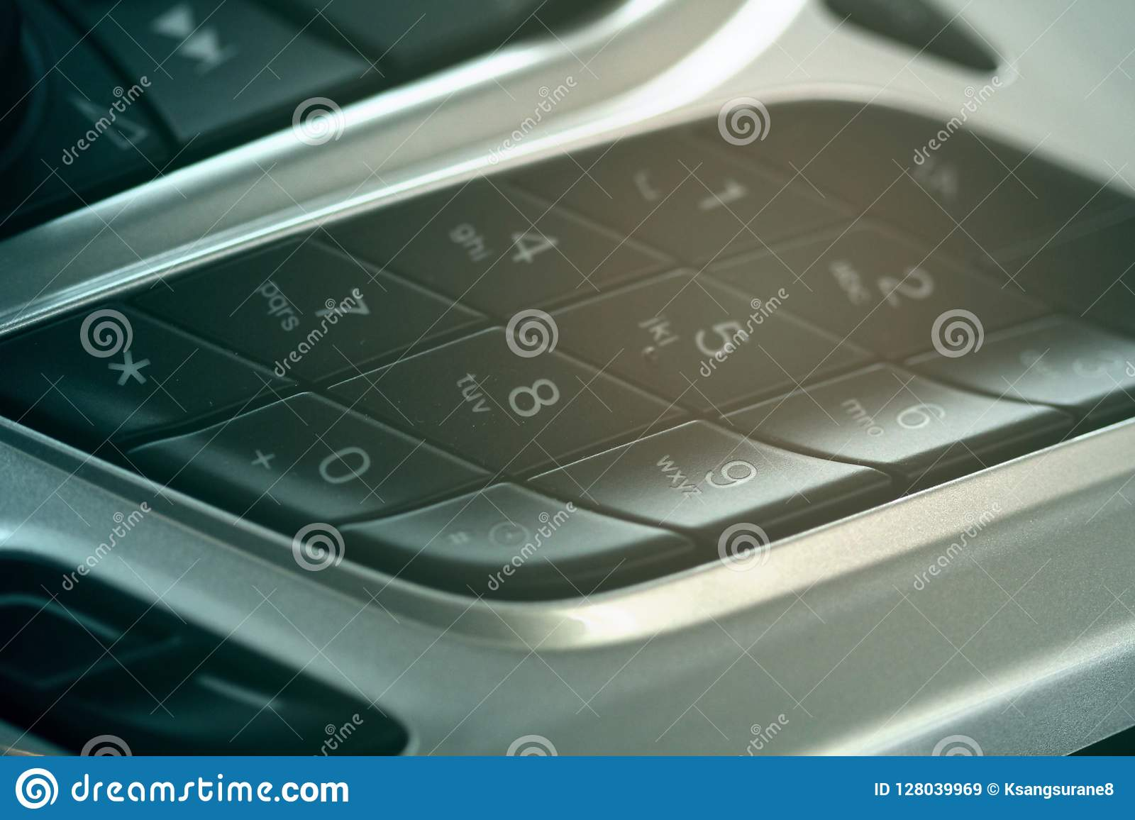 Car dashboard dial pad beside audio control buttons