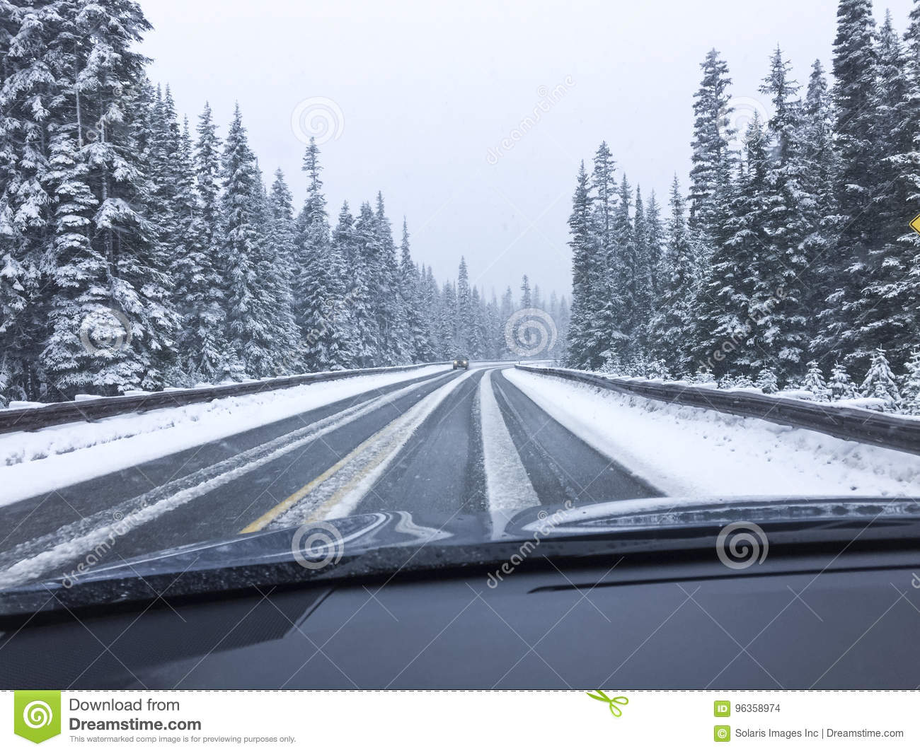 Car driving on snow-covered snowy mountain road in winter snow. Driver`s point of view viewpoint looking through windshield.