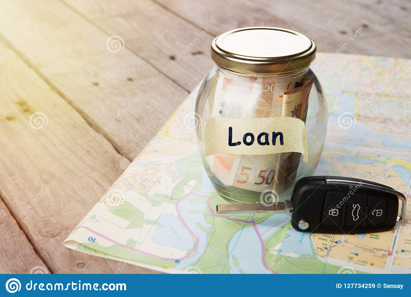 Car finance concept - money glass with word Loan, car key