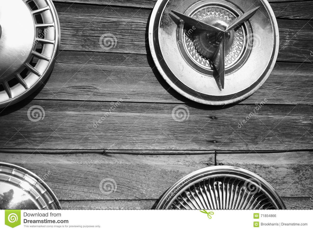 Car hubcaps hanging on aged wood wall