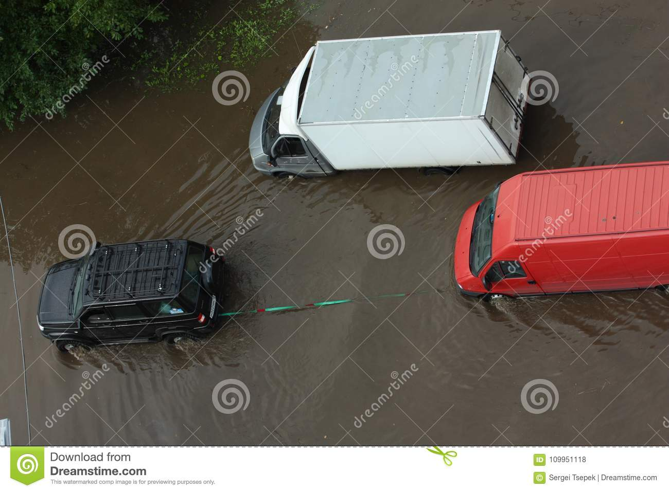 A car jeep towing a truck with stalled engine via flooded road