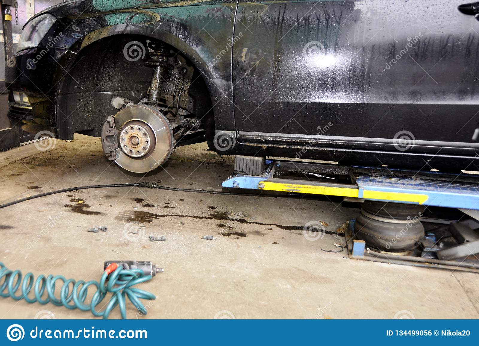 The car lifted by a pneumatic jack, wheel replacement