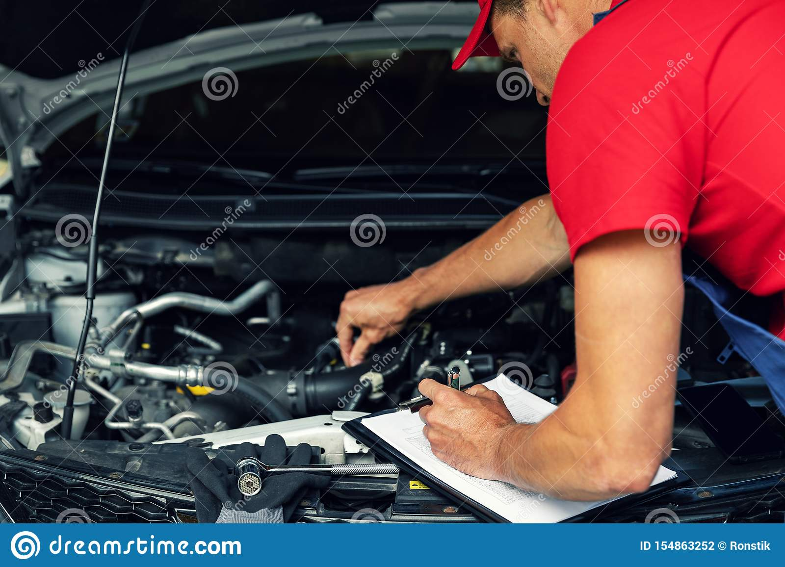 Car maintenance - mechanic check the engine and writing in checklist
