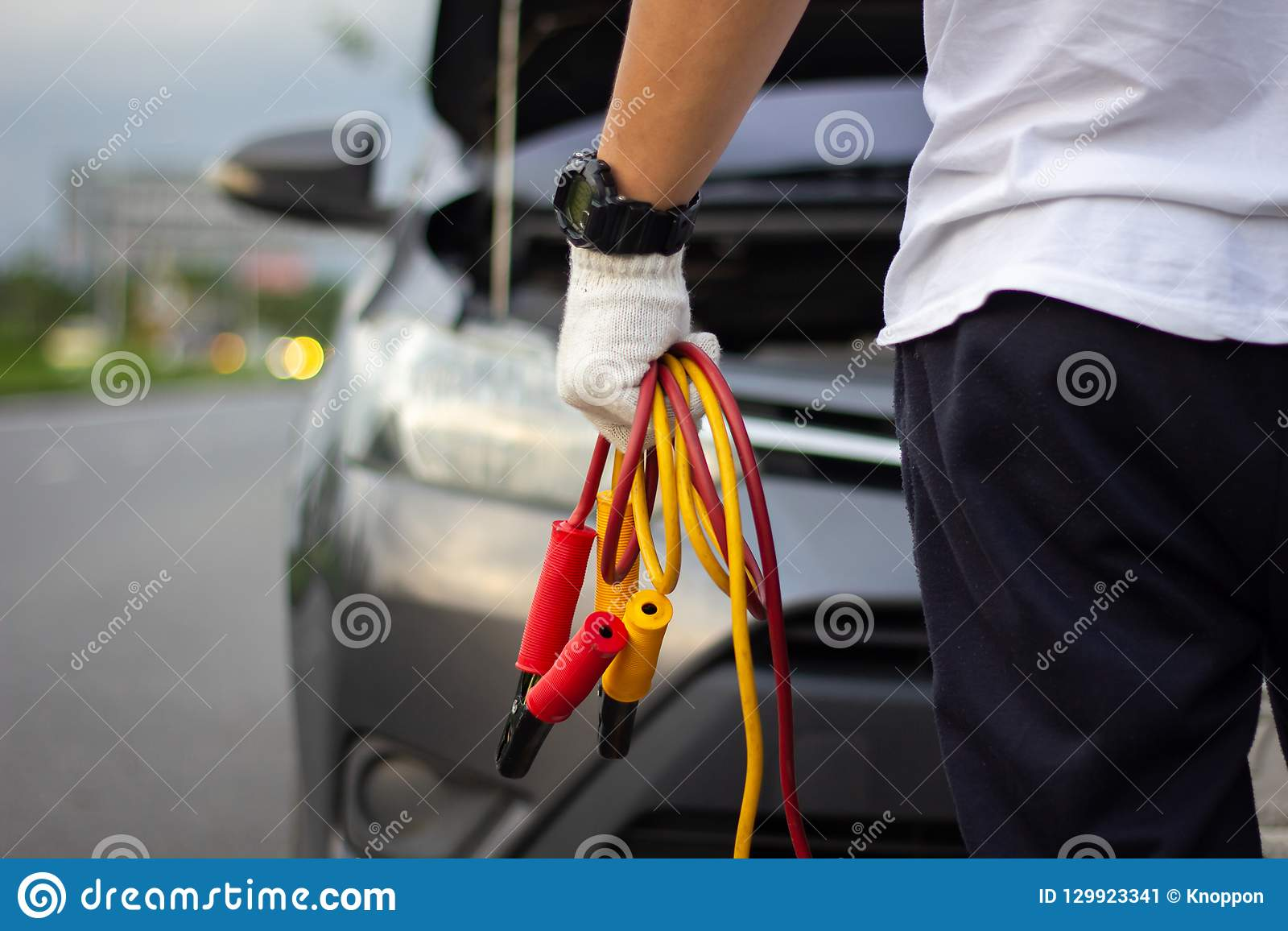 Car mechanic man holding battery jumper cables to charge a dead