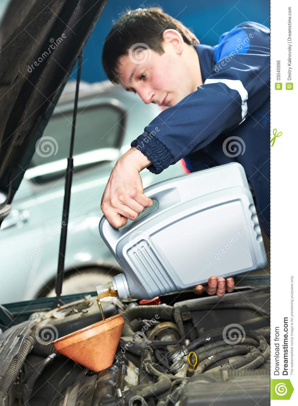 Car mechanic pouring oil into motor engine stock photo for Motor vehicle repair license