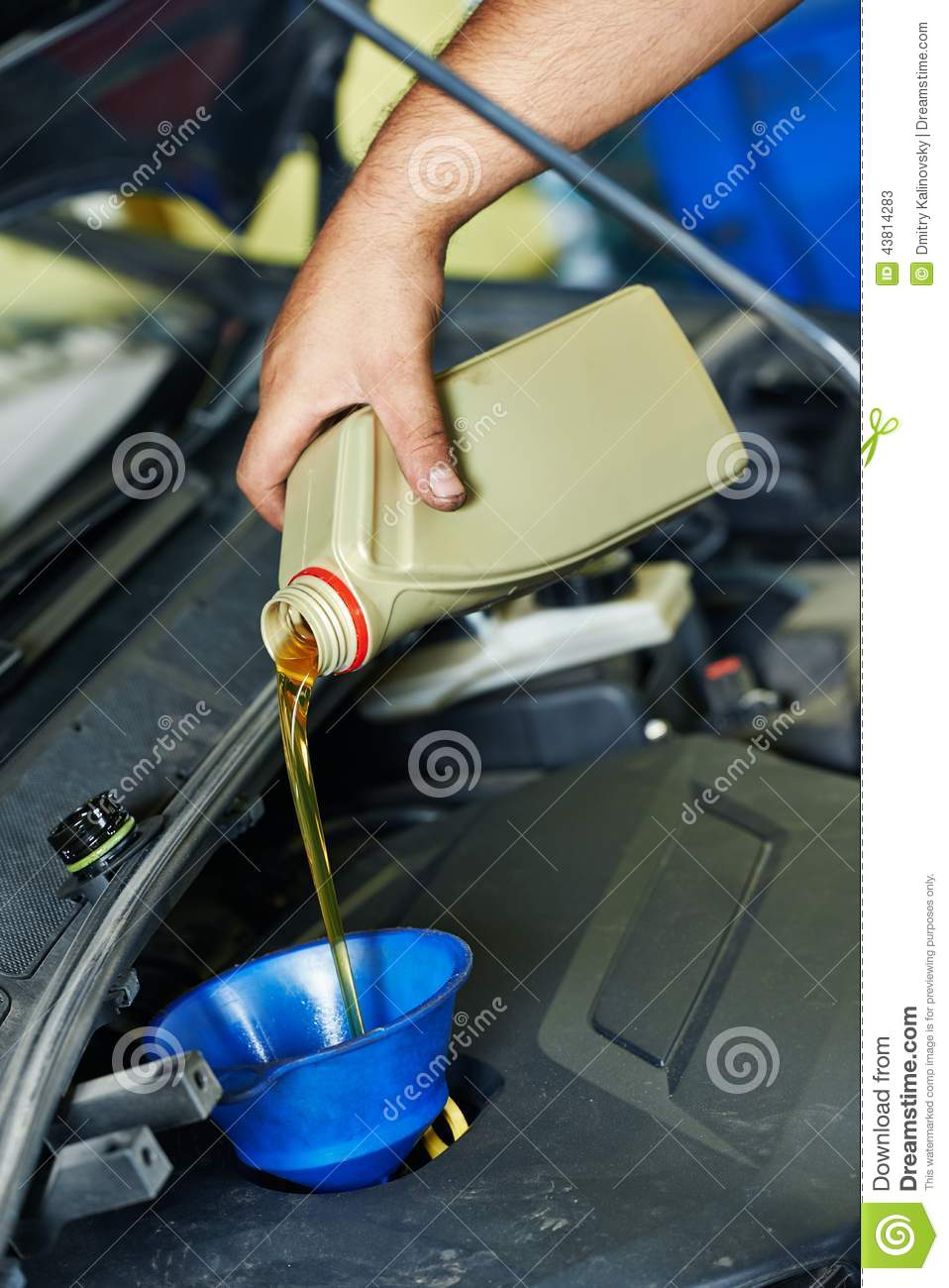 Car mechanic pouring oil into motor engine stock photo Motor vehicle repair