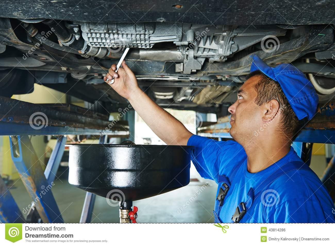 Car Mechanic Replacing Oil From Motor Engine Stock Photo