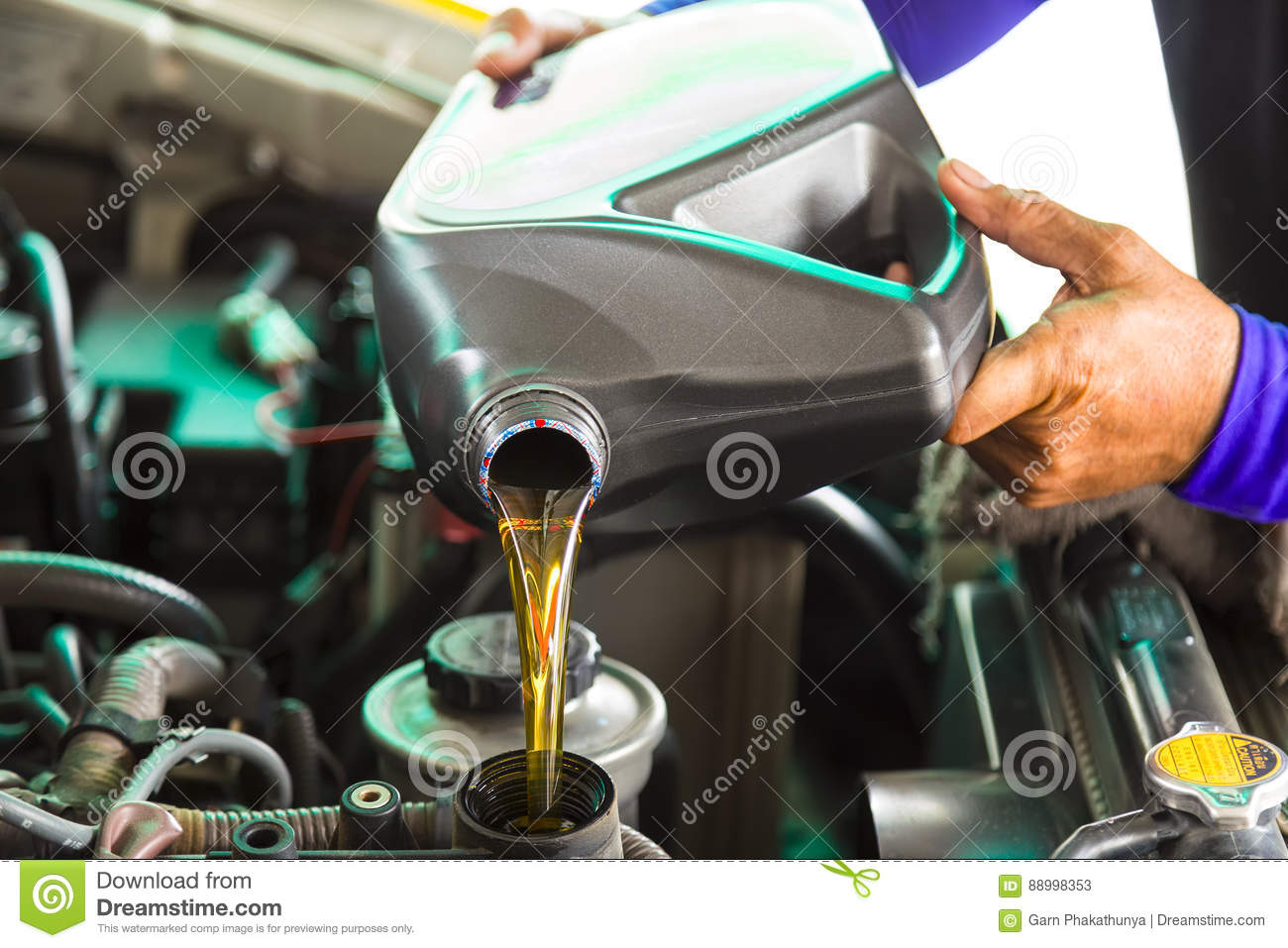 Car mechanic replacing and pouring fresh oil into engine at main