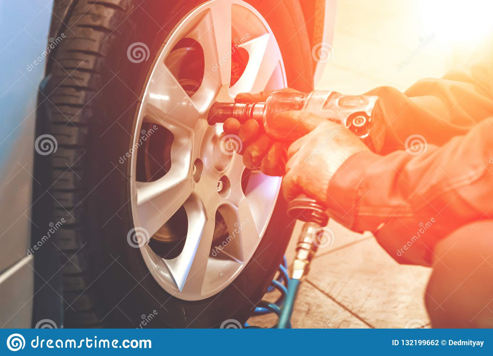 Car mechanic worker doing tire or wheel replacement with pneumatic wrench in garage of repair service station, sunlight effect