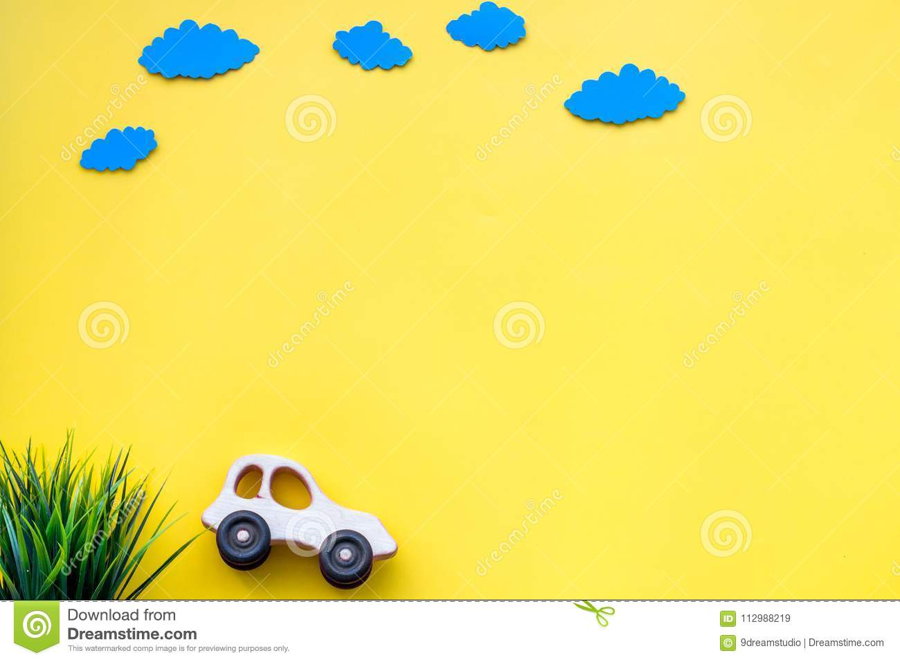 Car model and paper clouds for family traveling with child on yellow background top view mock-up