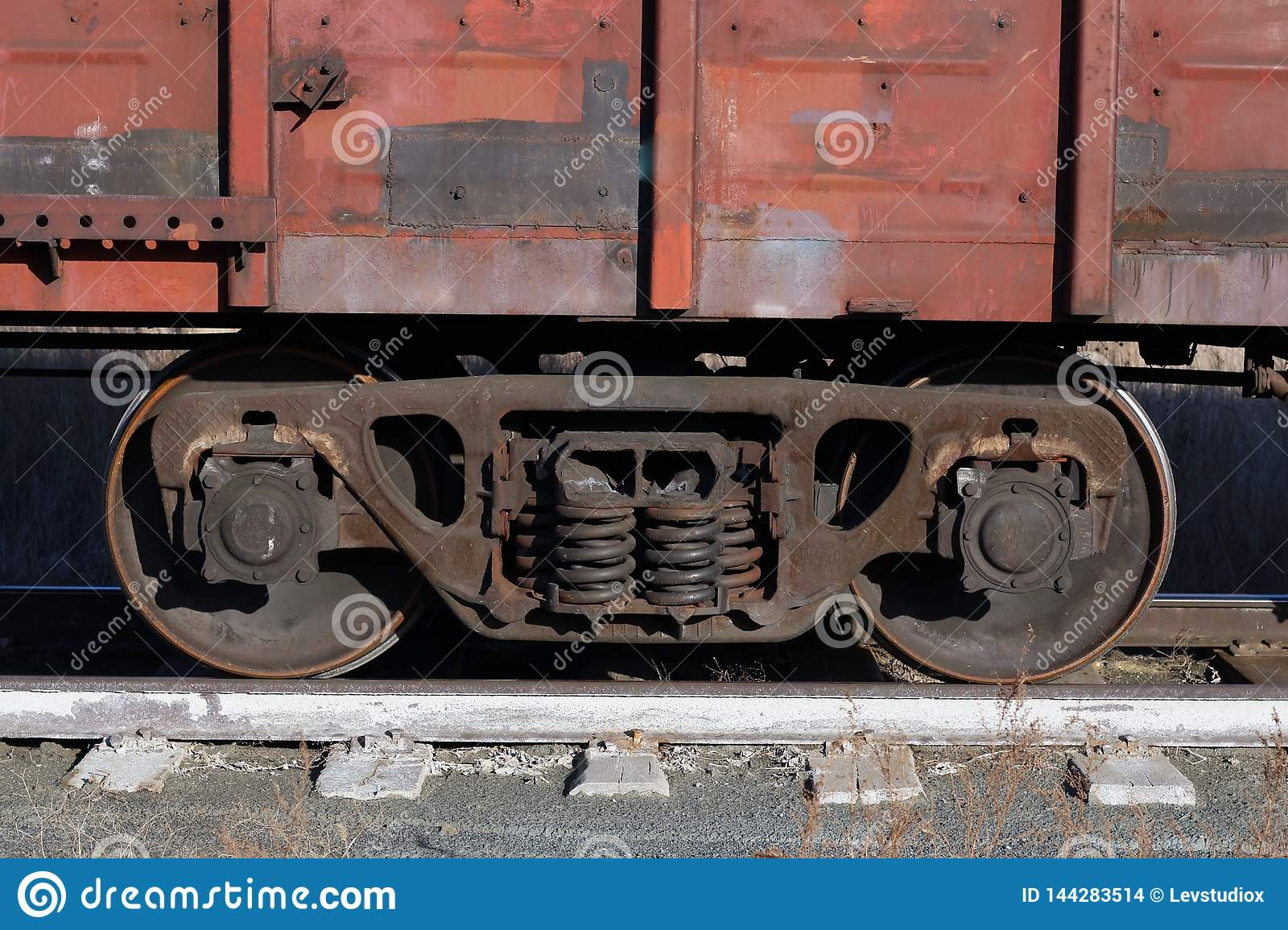 Wagon of an old rusty freight train stands on the rails
