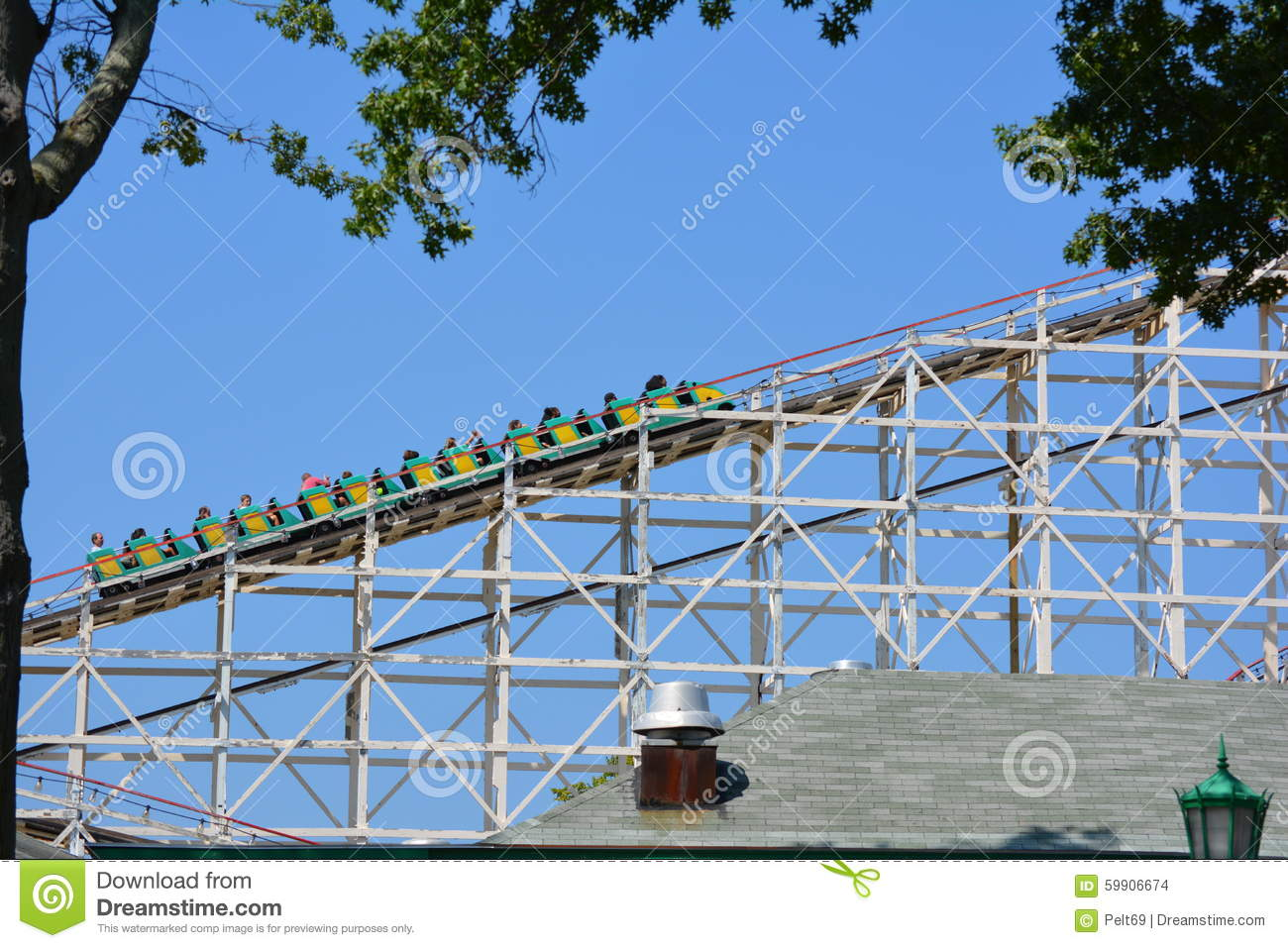 Vintage Backyard Roller Coaster :  on rails of old wooden roller coaster against blue skies on sunny day