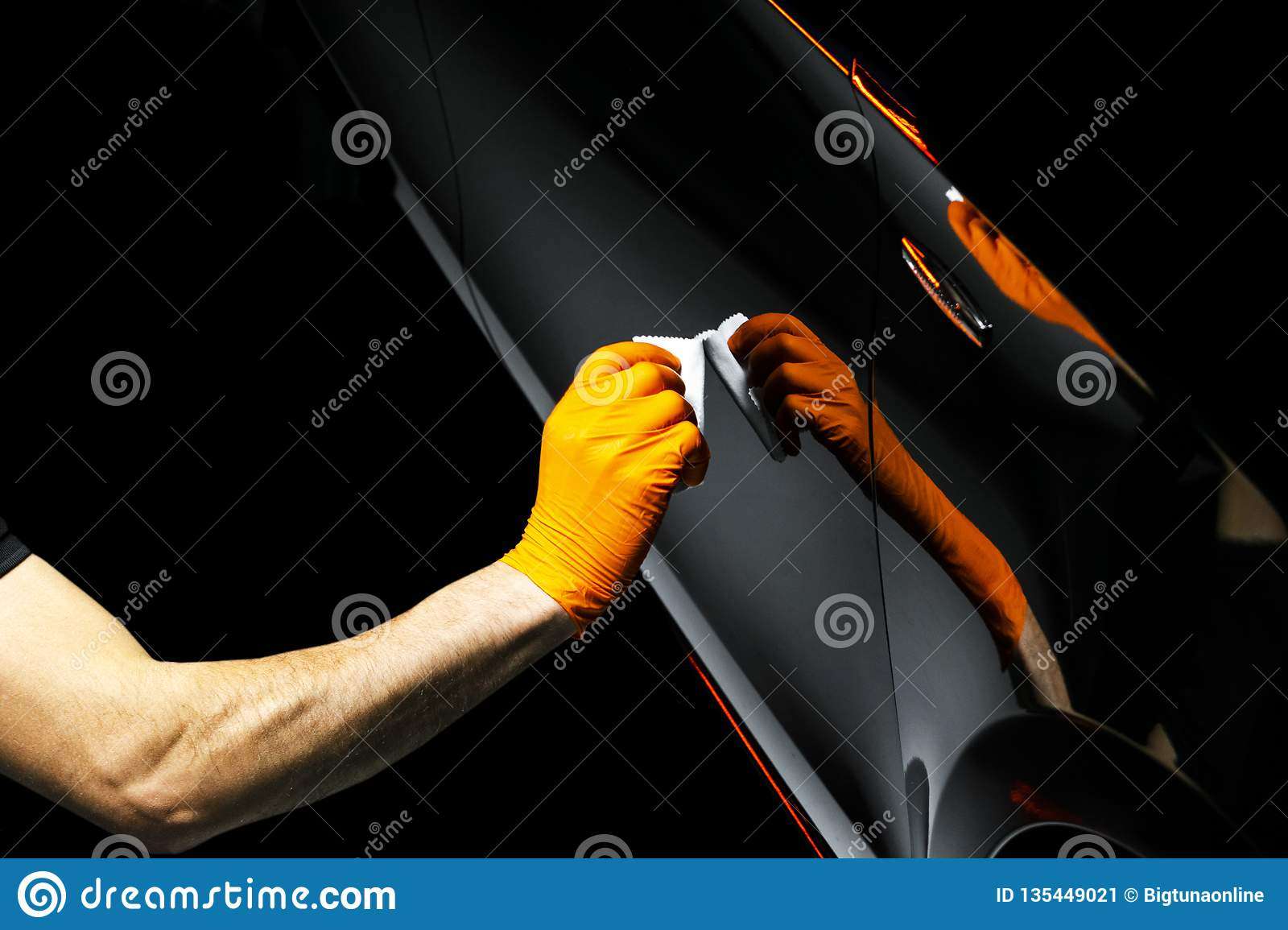 Car polish wax worker hands polishing car. Buffing and polishing vehicle with ceramic. Car detailing. Man holds a polisher in the