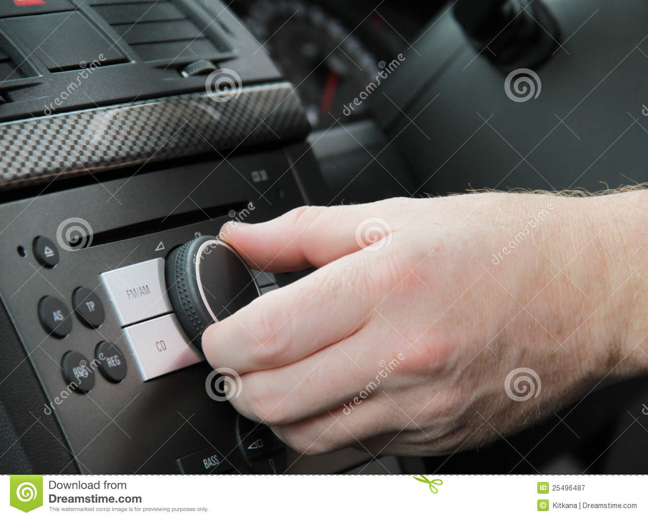 The right hand of an adult male driver adjusting the sound volume in the  car stereo