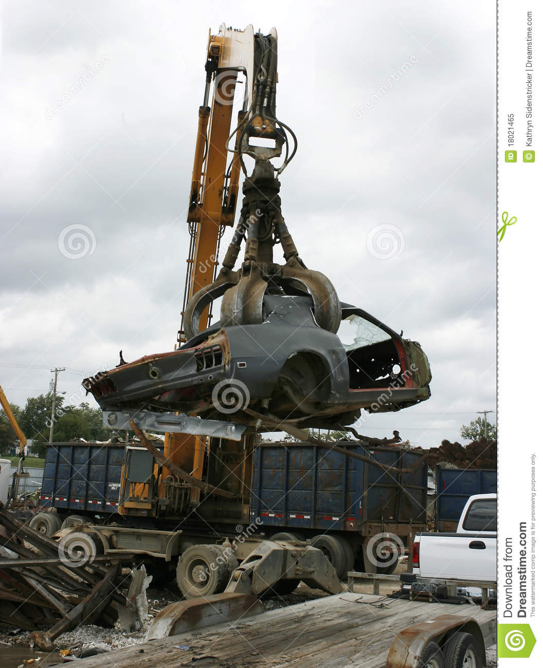 A 1969 ford mustang is picked up by a grappling crane for recycling or crushing