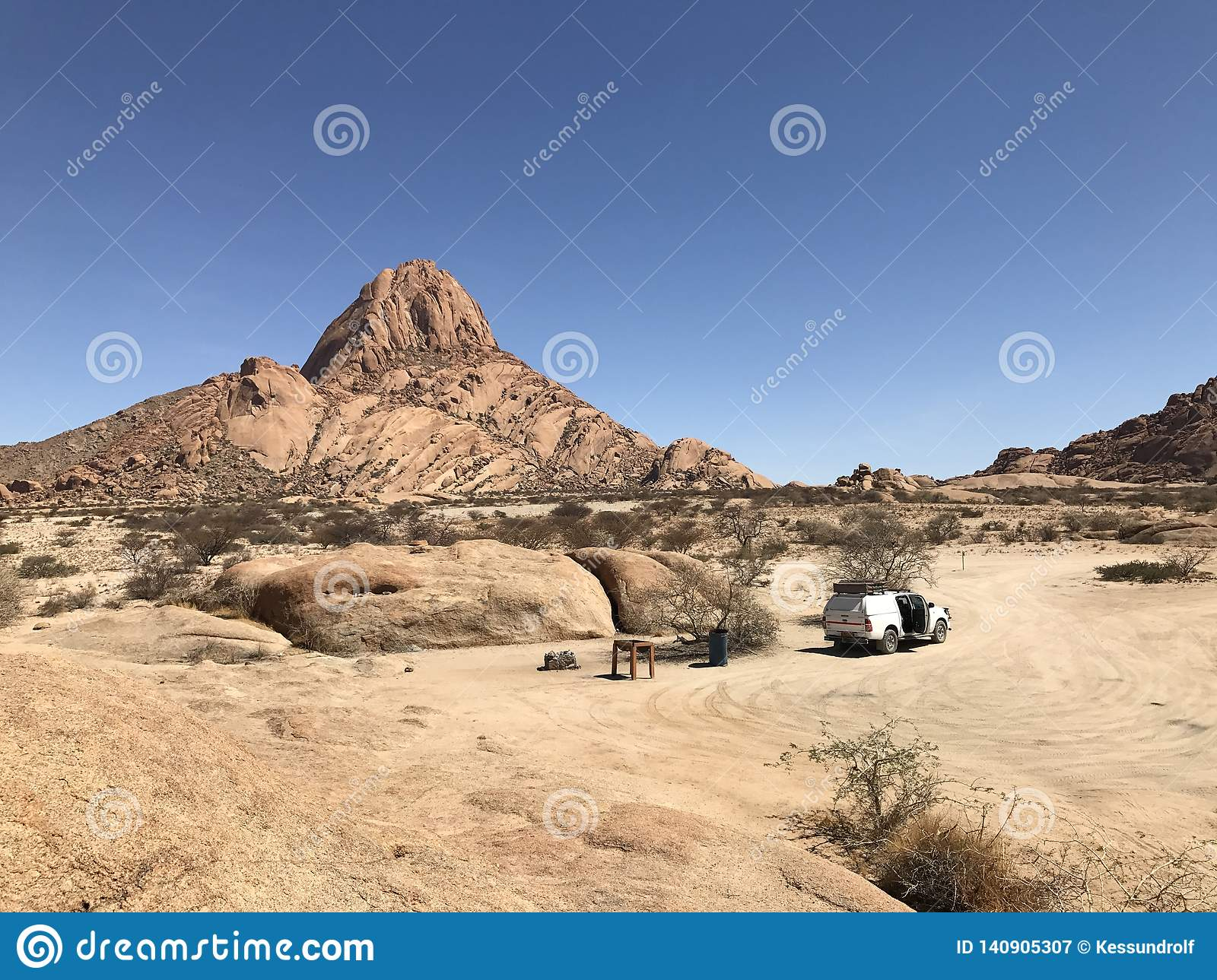 Car with roof tent on desert campsite