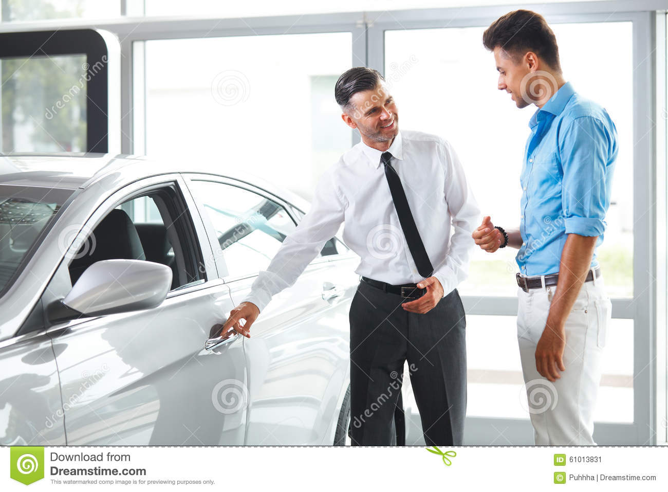 car sales consultant showing a new car to a potential buyer in s stock image image of salesman. Black Bedroom Furniture Sets. Home Design Ideas