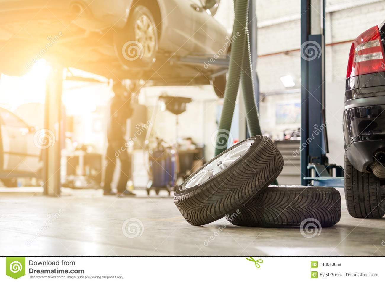 Car service center. Vehicle raised on lift at maintenance station. Auomobile repair and check up