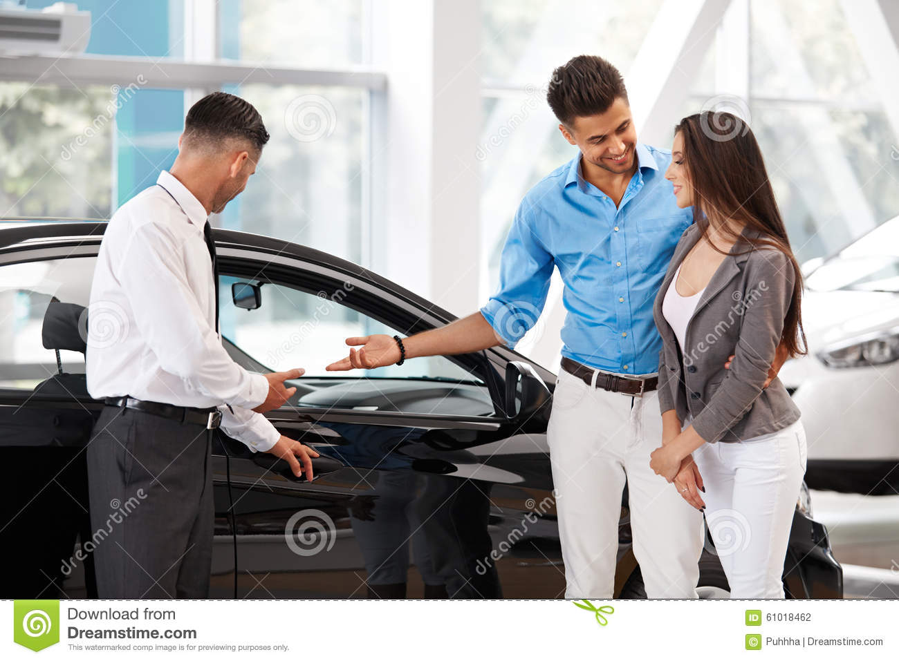 car showroom young couple buying a new car at dealership stock photo image 61018462. Black Bedroom Furniture Sets. Home Design Ideas