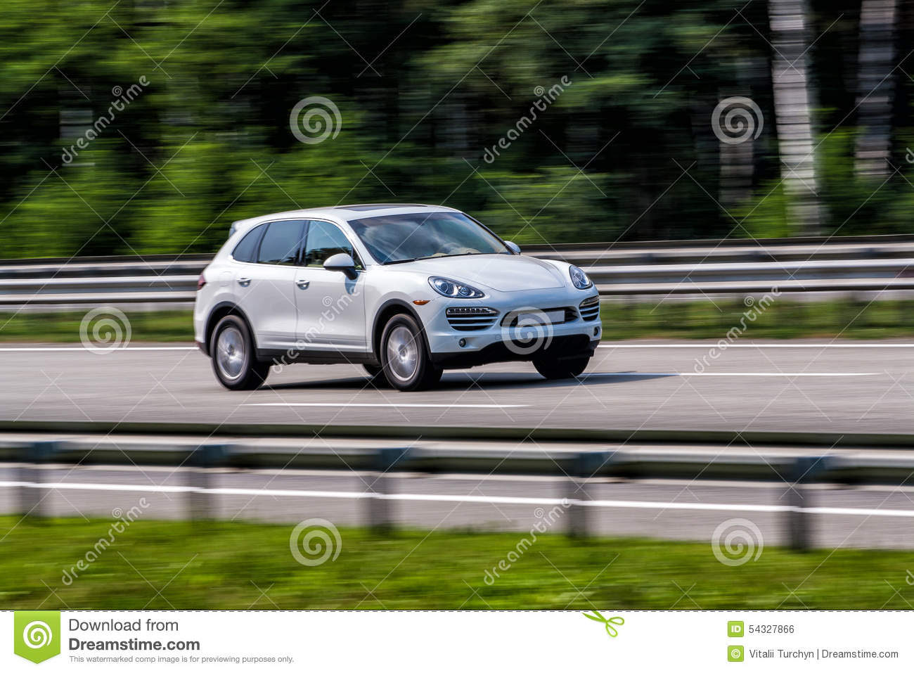 Luxury white Porsche Cayenne speeding on empty highway