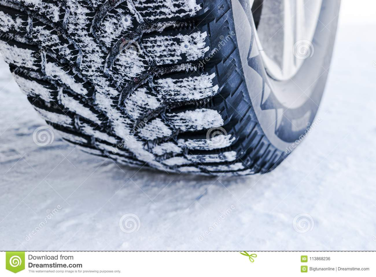 The car tire in the snow close up. Car tracks on the snow. Traces of the car in the snow. Winter tires. Tyres covered with snow at