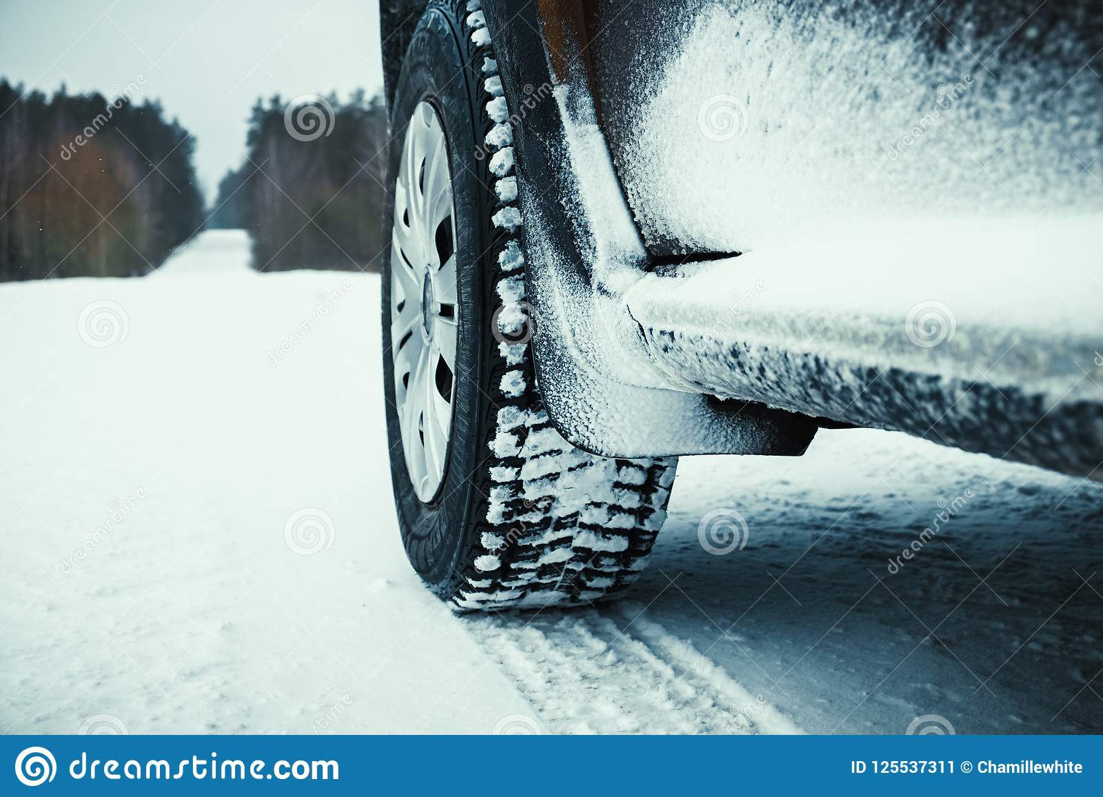 Car tires covered with snow on winter road.