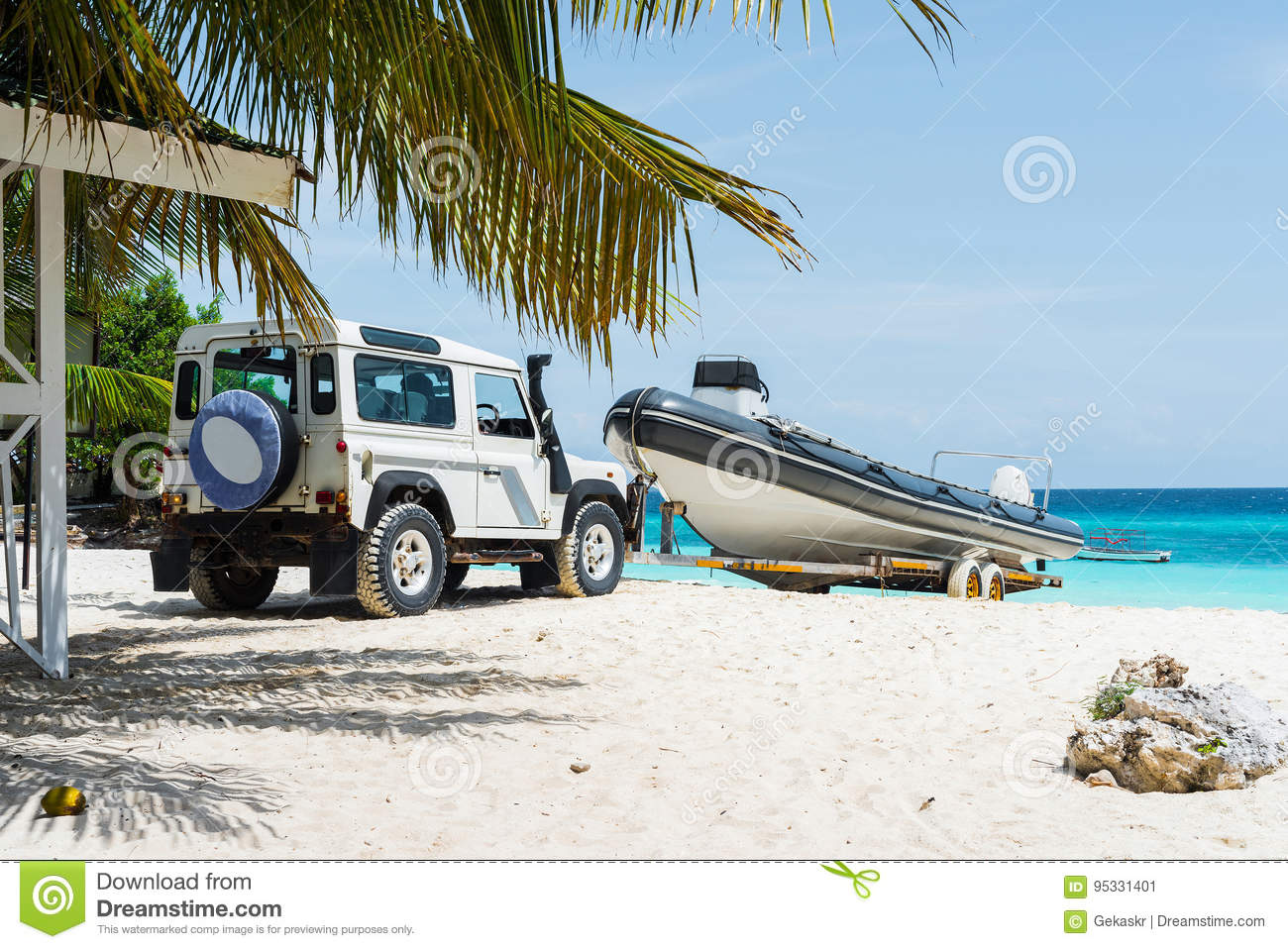 Car transporting motorboat on african beach