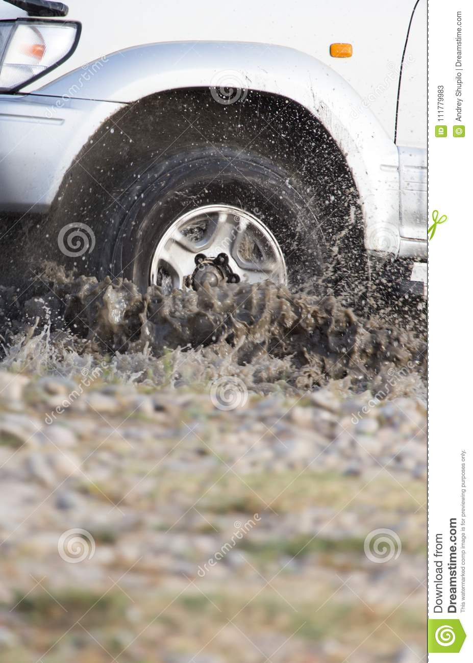 Car wheel in a spray of dirt and water