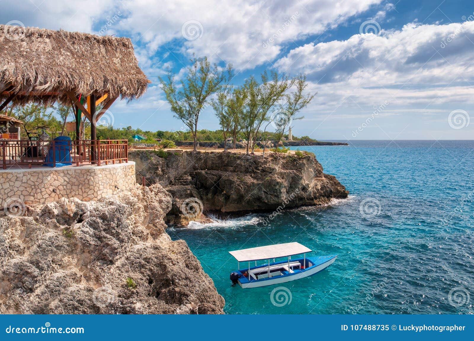 Caraïbisch rotsachtig strand met turkoois water, toeristenboot en vuurtoren in Negril Jamaïca