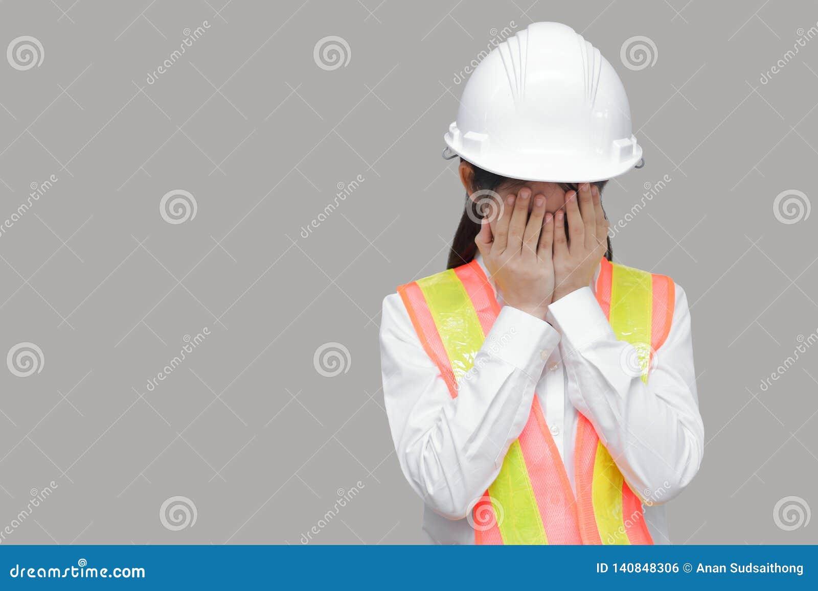 Cara asiática nova forçada Tired da coberta do trabalhador com mãos no fundo isolado cinzento