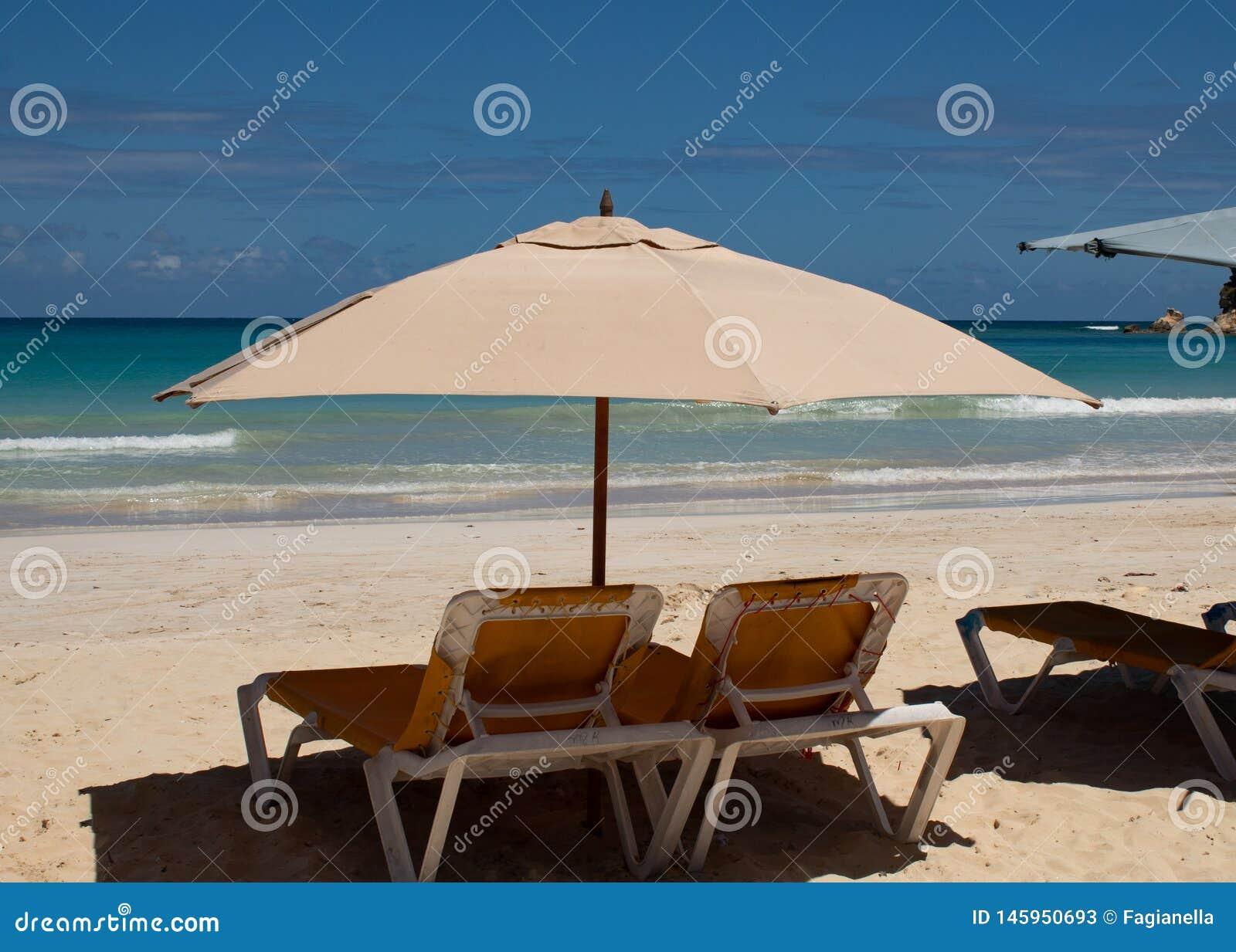 Cara?bische kleuren: sunbeds en paraplu s op openbaar strand, intense blauwe overzees en hemel: tropisch paradijs