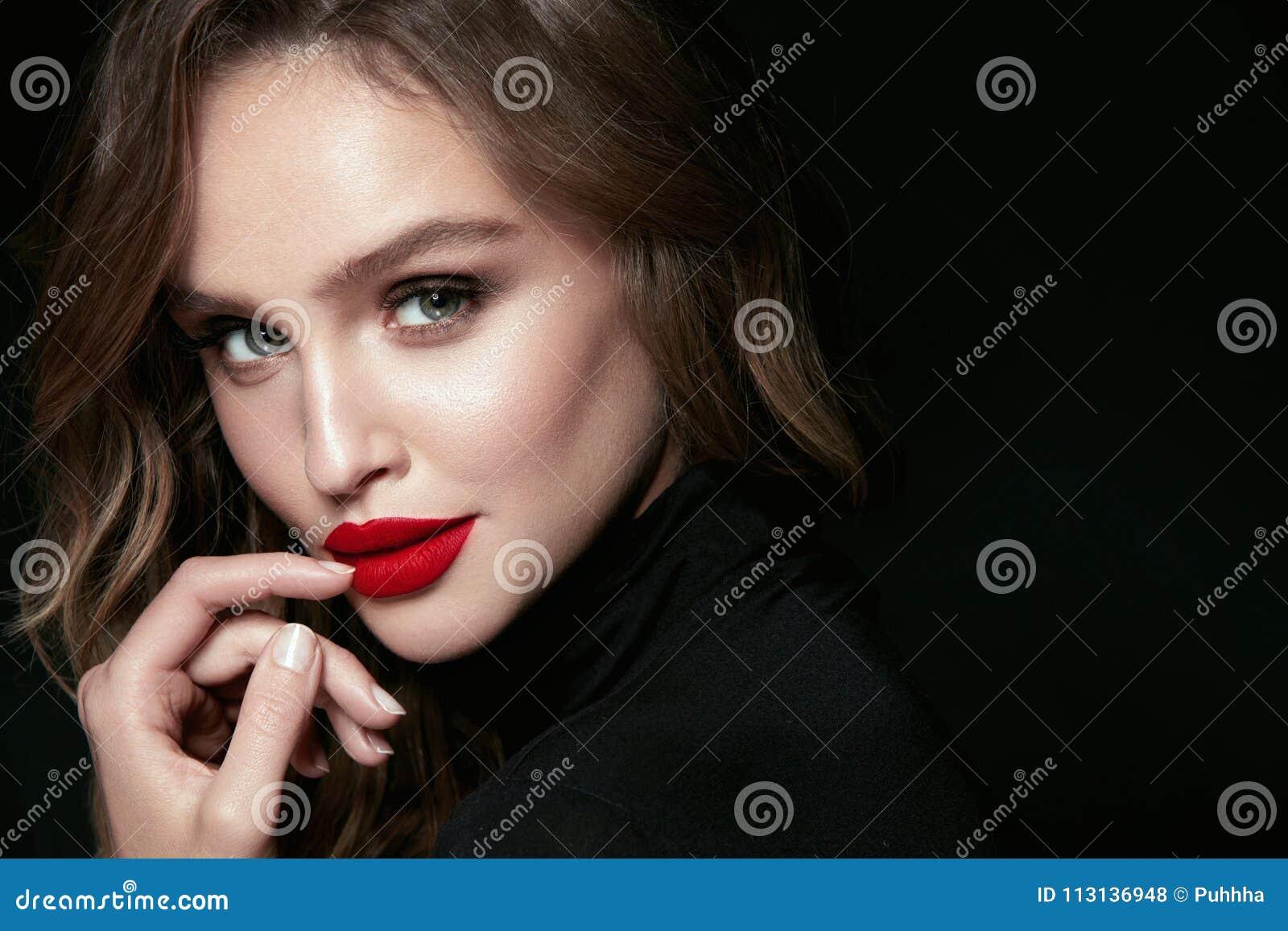 Cara bonita da mulher com composição e os bordos vermelhos