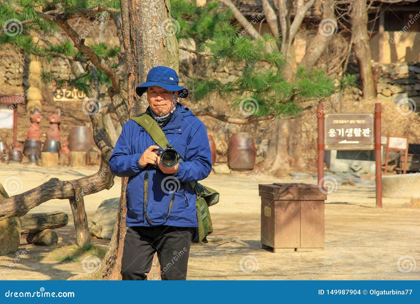 Cara completa aposentada do homem coreano superior que guarda uma câmera na mola adiantada da vila popular de Minsokchon, Yongin,
