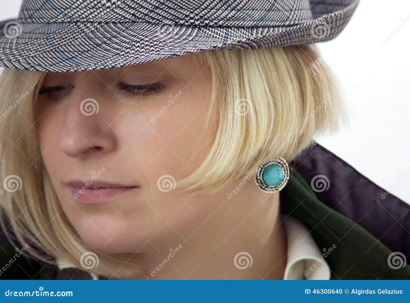 A cara da mulher com um brinco ciano