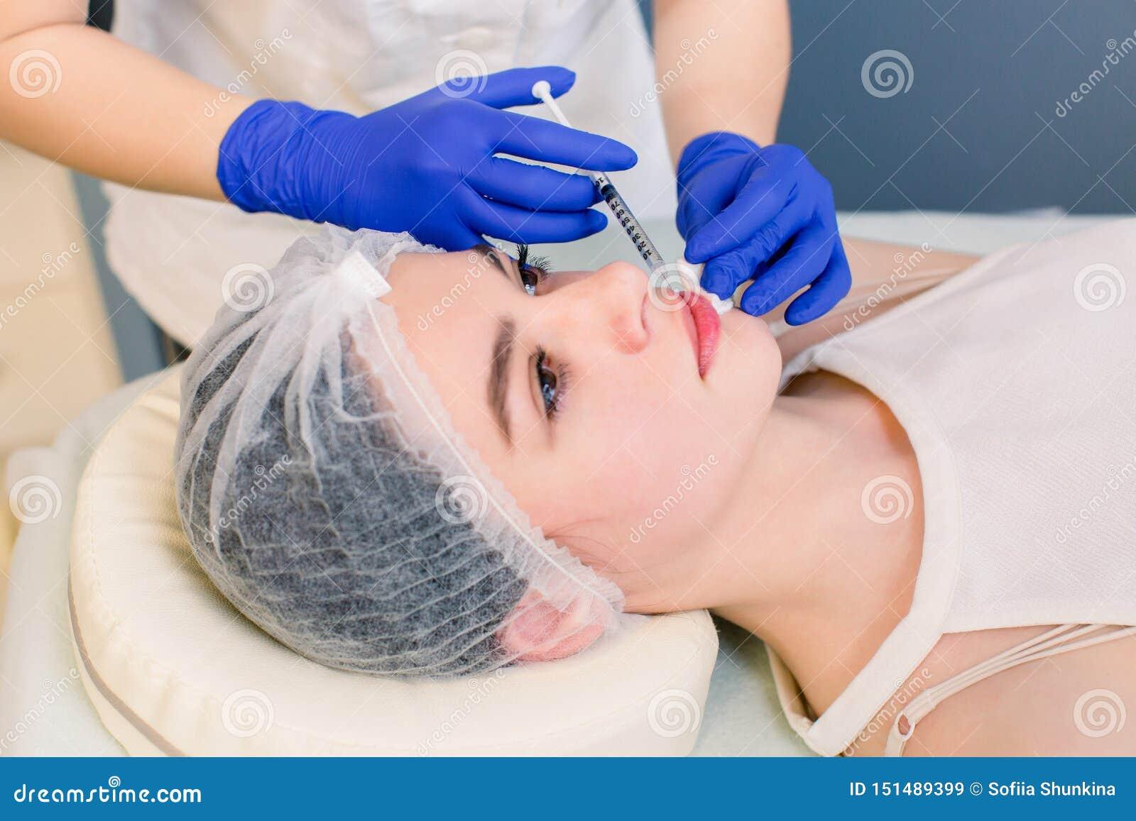 Cara da mulher do conceito da beleza da correção da cirurgia de plástico da cosmetologia dos bordos e mão morenos novas do doutor